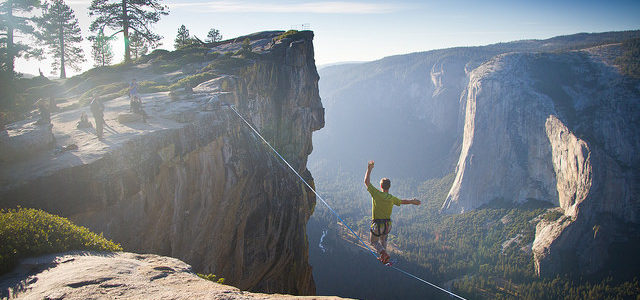 man walking tightrope across canyon
