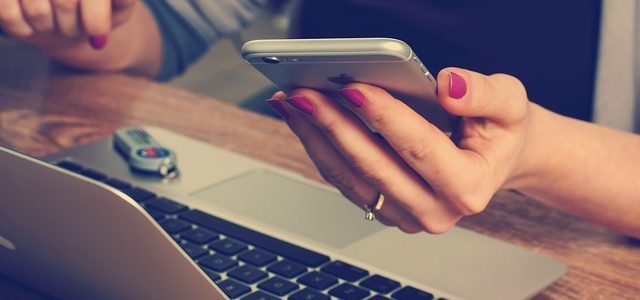 woman at laptop with iphone